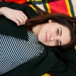 Portrait of a beautiful young female lying on the grass — Stock Photo