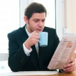 Businessman having breakfast and reading newspaper — Stock Photo