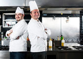 Portrait of two chefs smiling and holding kitchen utensil — Stock Photo