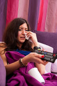 Young female crying while watching film — Stock Photo