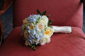 Wedding bouquet sitting in chair — Stock Photo