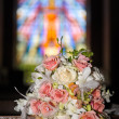 Wedding bouquet in front of stained glass — Stock Photo