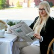 Stock Photo: Womis reading newspaper