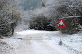 Snowy mountain road with a road sign — Stock Photo