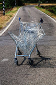 Broken shopping cart in a street campaign — Stock Photo