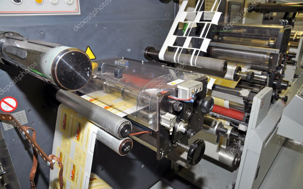 UV flexo press for printing label. Flexography (also called surface printing), often abbreviated to flexo, is a method of printing most commonly used for packaging (labels, tape, bags, boxes, banners.   Stock Photo #9939756