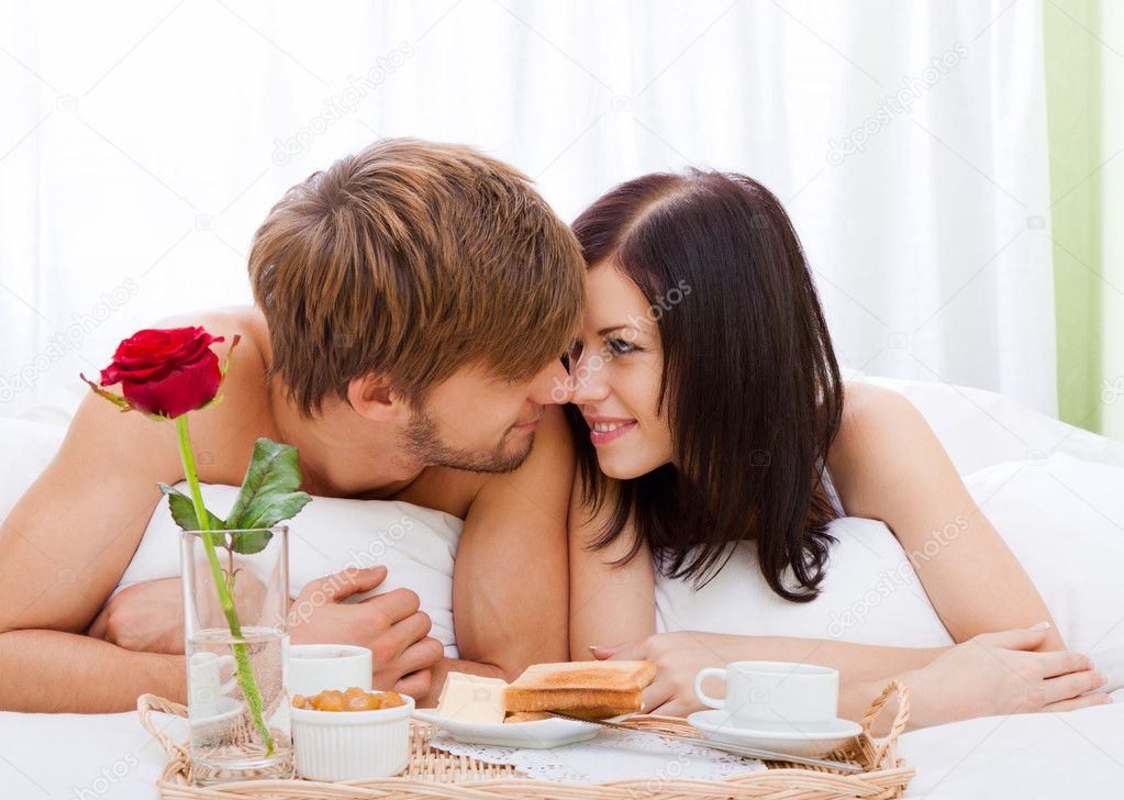 Beautiful young happy couple lying in bed — Stock Photo #10011013