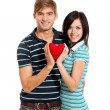 Young love couple holding red heart — Stock Photo