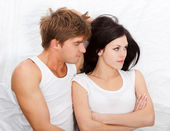 Young upset couple in bed — Stock Photo
