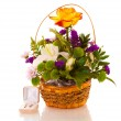 Stock Photo: Flowers in a basket and gold earrings.isolated.