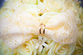Wedding rings on white wedding flowers. — Stock Photo