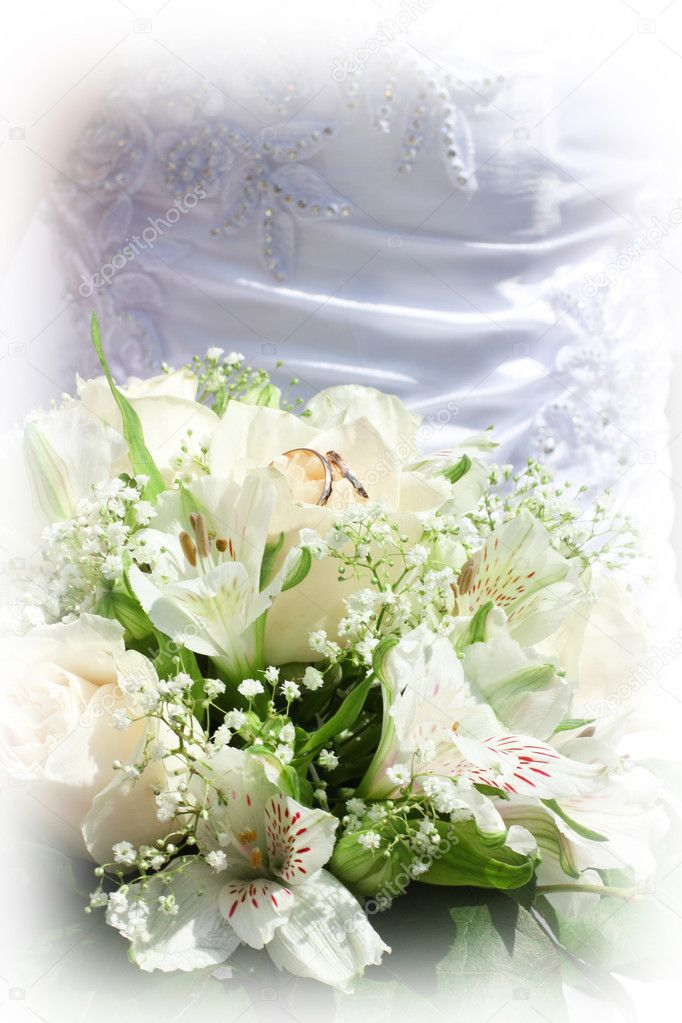Wedding bouquet about wedding rings, against a wedding dress.  Stock Photo #10199149