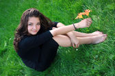 Girl about a flower, on a grass. — Stockfoto