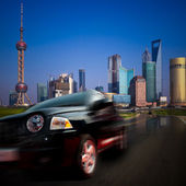 Fast car moving from a modern city.the background with the landmark of shanghai china. — Stock Photo