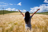 The girl stand in the wheaten field. — Stock Photo