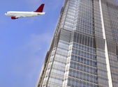 Airplane and the modern building — Stock Photo