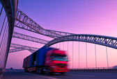 Truck speeding through a bridge at sunset,motion blur. — Stock Photo
