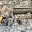 Wheel loader machine unloading rocks — Stock Photo
