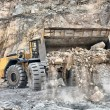 Wheel loader machine unloading rocks — Stock Photo #10235844