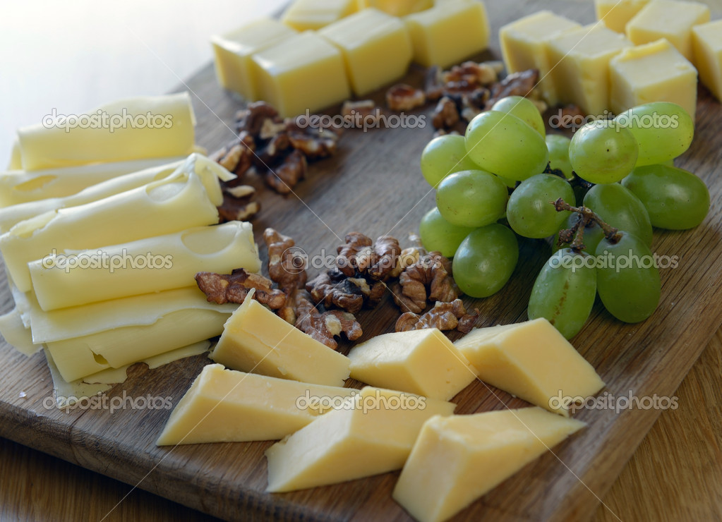 Set  cheese on a wooden board with grapes and nuts  Stock Photo #10239980