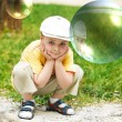 Soap bubble. The boy on a nature — Stock Photo