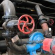Red valve and electric water pumps at power plant - Foto Stock