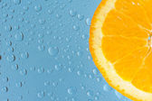 Orange med många vattendroppar på blå bakgrund — Stockfoto