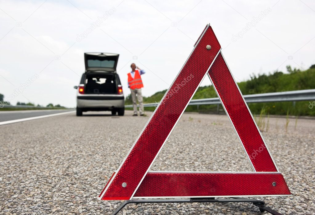 Road side warning triangle, warning oncoming traffic of a broken down car, with a man using his cell phone to call for assistance — Stock Photo #8389182