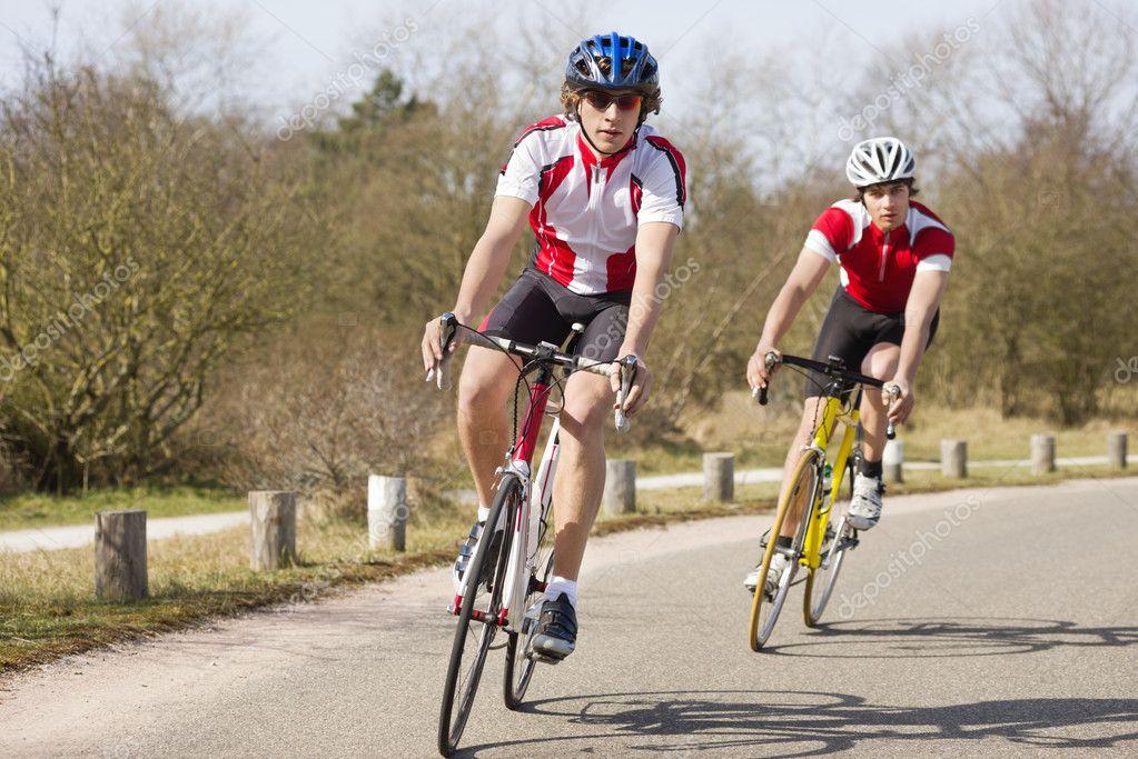 Two cyclists leaning inwards in the curve of a road during a training tour on a sunny spring day — Stock Photo #9802061