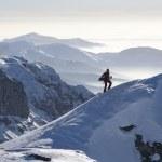 Man climbing a peak with snowboard — Stock Photo