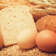 Wheat bread, grain and ears with eggs - Stock Photo