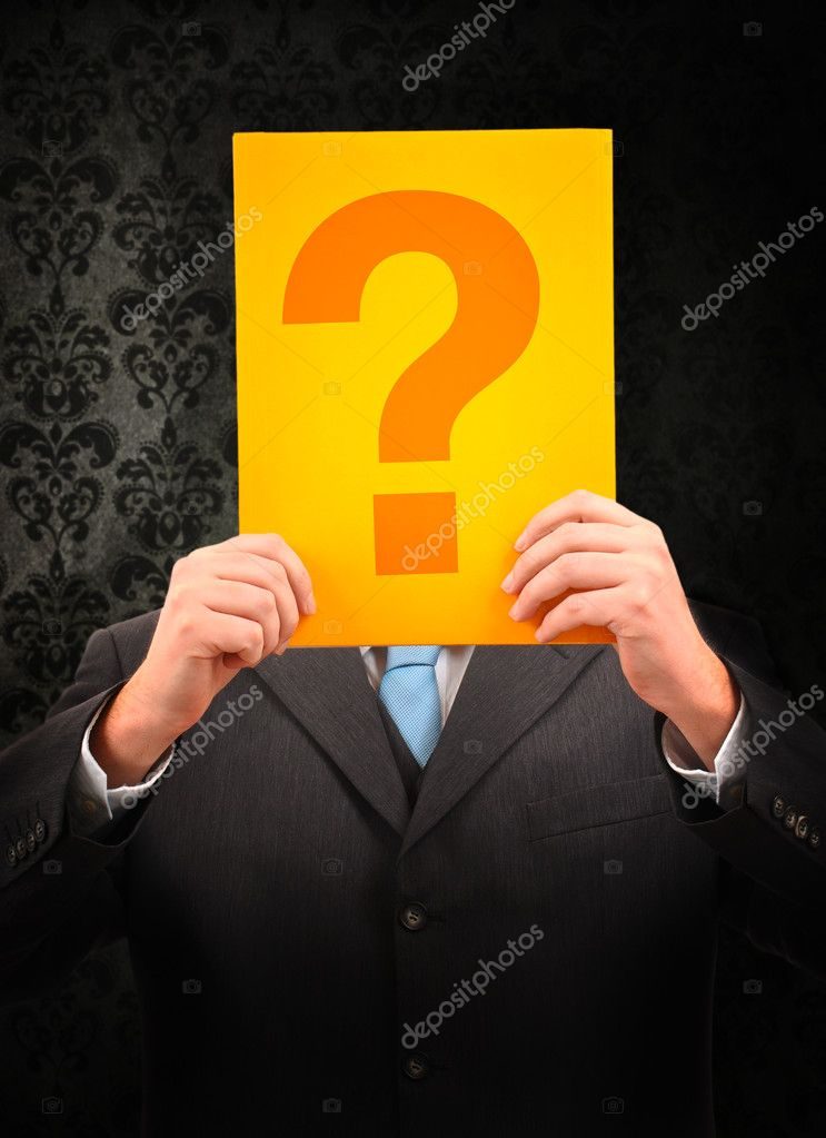 Businessman holding question mark in front of his head on vintage background  Stock Photo #10239758