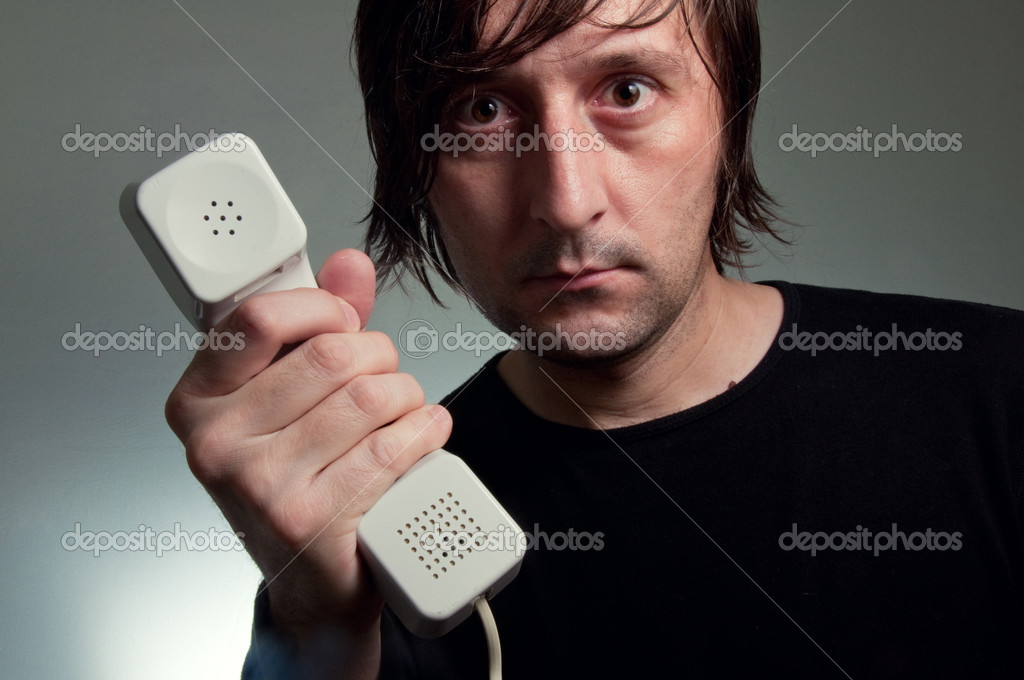 MAn in black shirt holding a telephone, SOS line concept. — Stock Photo #8809175