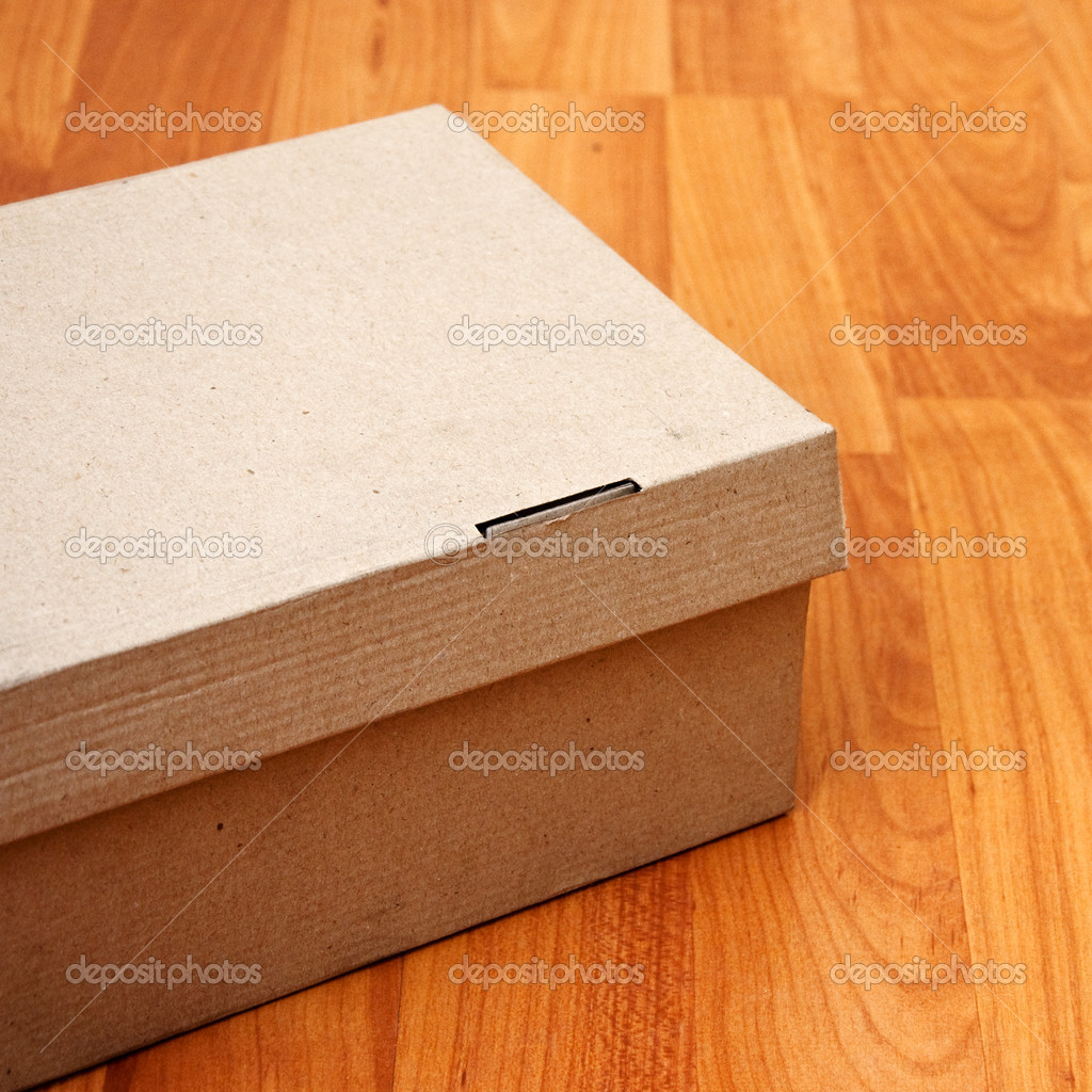 Cardboard box on a laminated wooden floor. — Stock Photo #9523975