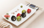 Delicious sushi rolls on white plate with chopsticks and wasabi. — Stock Photo