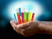 Verrerie de laboratoire différents avec liquide de couleur sur les mains — Photo