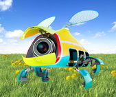 Security flay mini camera over green grass background — Stock Photo