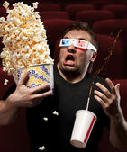 Very scared man watching 3D movie — Stock Photo