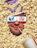 Face in popcorn watching 3D movie — Stock Photo