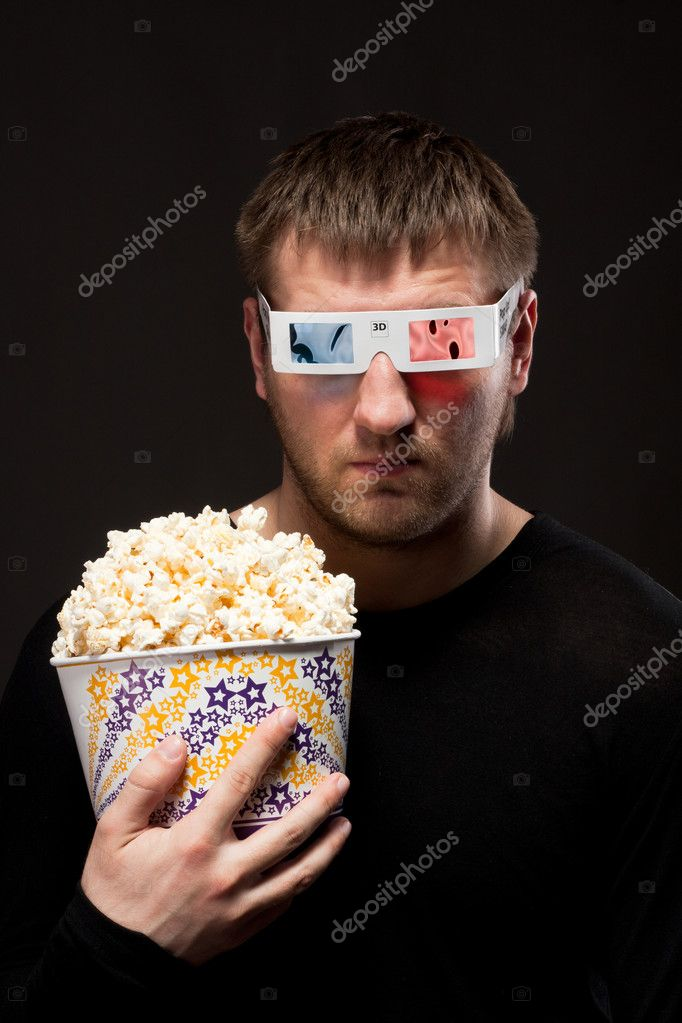 Portrait of serious man watching 3D movie and holding bucket of popcorn — Stock Photo #10024884