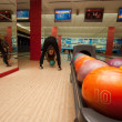 Funny beginner girl playing bowling — Stock Photo