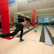 Stock Photo: Funny beginner girl playing bowling