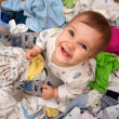Baby in heap of wear - Stockfoto