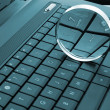 Magnifying glass on laptop - Stockfoto