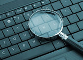 Magnifying glass on laptop — Stock Photo