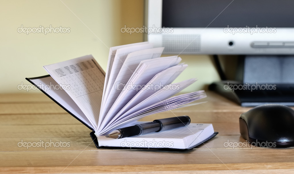 Pen in open agenda before a computer screen  Stock Photo #9897892