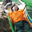 The young man has a rest in a hammock — Stock Photo #9766435