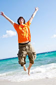 The young man jumps at the sea — Stock Photo