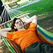 The young man has a rest in a hammock — Stock Photo #9985889