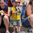 Stock Photo: Oung Boy Eating Frozen Treat While Watching Parade